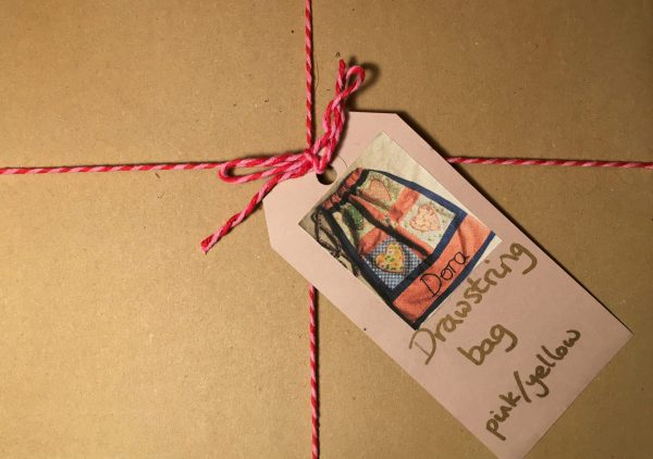 Drawstring bag box tied with some thread and a card label